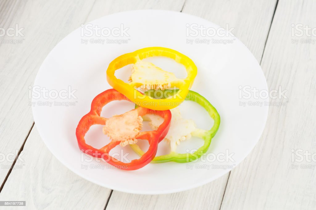 Three slices of colored red and green and yellow fresh ripe raw pepper in ceramic bowl on old rural white wooden planks royalty-free stock photo
