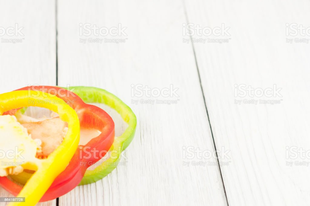 Three slices of colored red and green and yellow fresh ripe raw pepper on old rural white wooden planks royalty-free stock photo