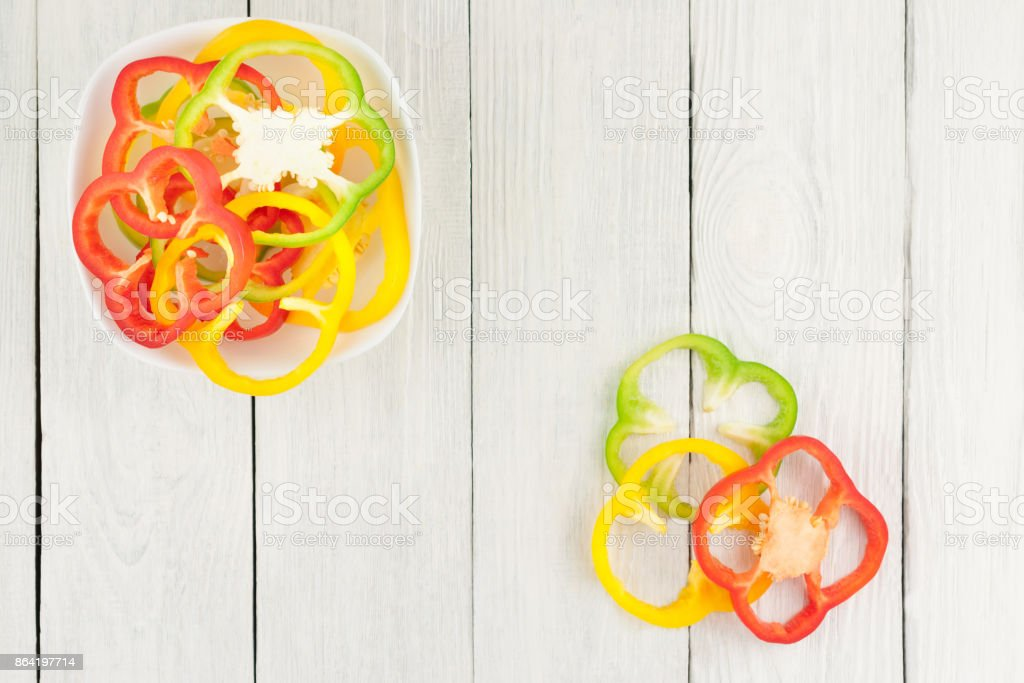 Three slices of colored red and yellow and green fresh ripe raw pepper beside heap of slices of pepper in ceramic bowl on old rural white wooden planks royalty-free stock photo