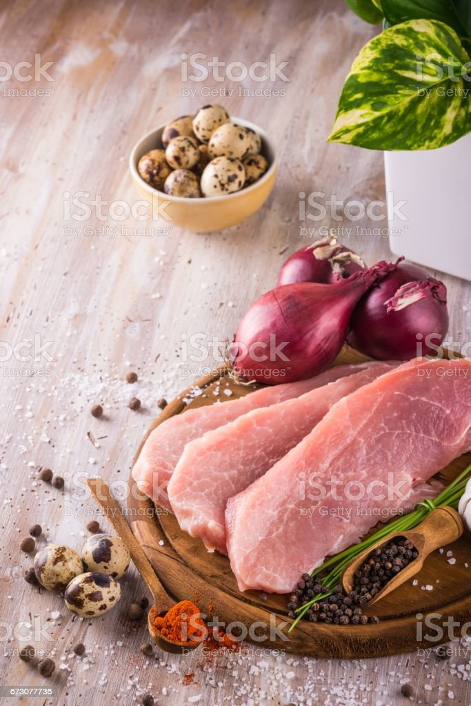 Three slices of raw pork meat on wooden plate stock photo