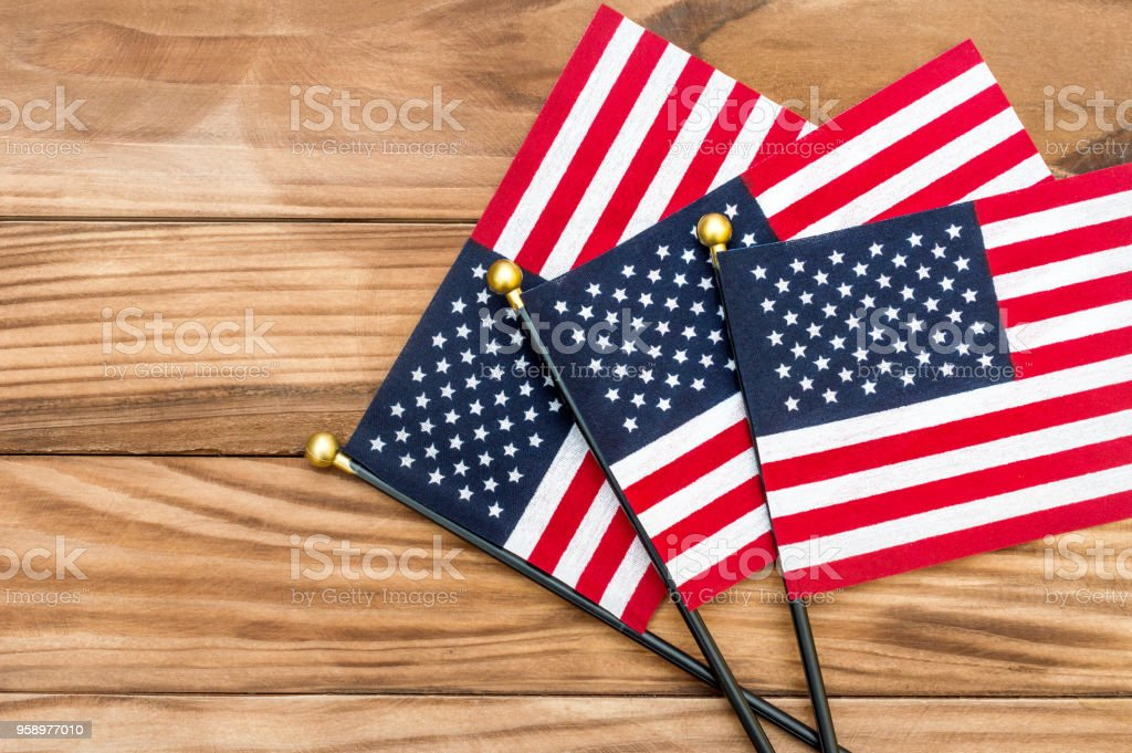 7f2a07e84f5e Three small american flags on wooden background. Top view. Copy space. -  Stock image .