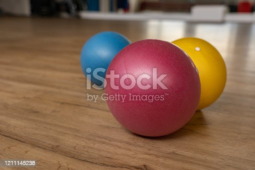 Three small and colorful gymnastic balls on wooden floor of a gymnastic hall of a group fitness center. Reflections of mirror in background. Low angle view.