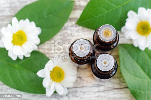 istock Three small bottles with essential oils. Old wooden background with green leaves and daisy flowers. Aromatherapy, spa and herbal medicine concept. Copy space, top view. 1198026755