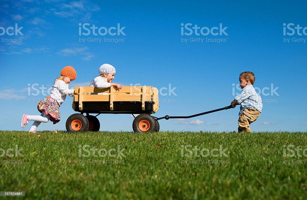 Drei kleine Kinder Schieben, Ziehen und Spielen mit Wagon – Foto