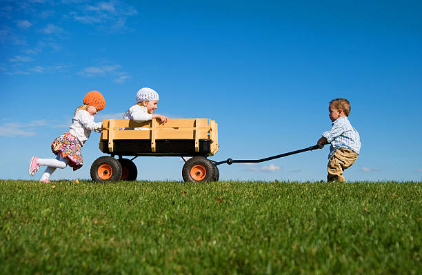 Three Small Children Pushing, Pulling and Playing with Wagon stock photo