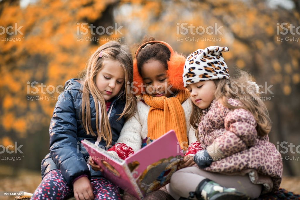 Three small girls reading a children's book in autumn day. stock photo