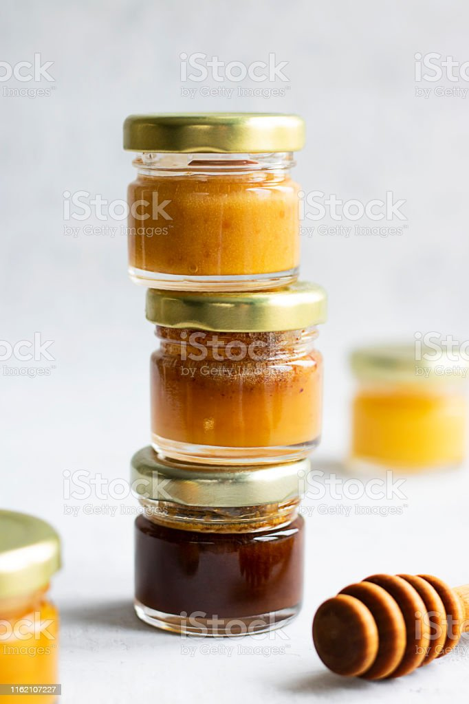 Three Small Glass Jar Pyramid Close Up Of Honey With Metal Cap And