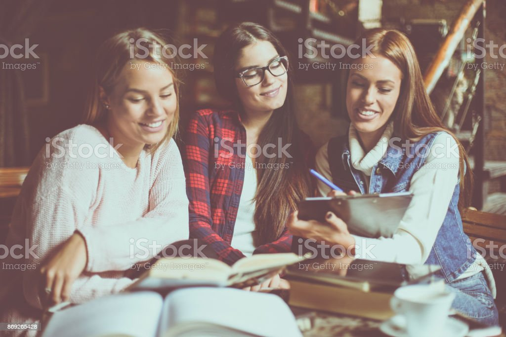 Three smiley young students girl working homework together. stock photo