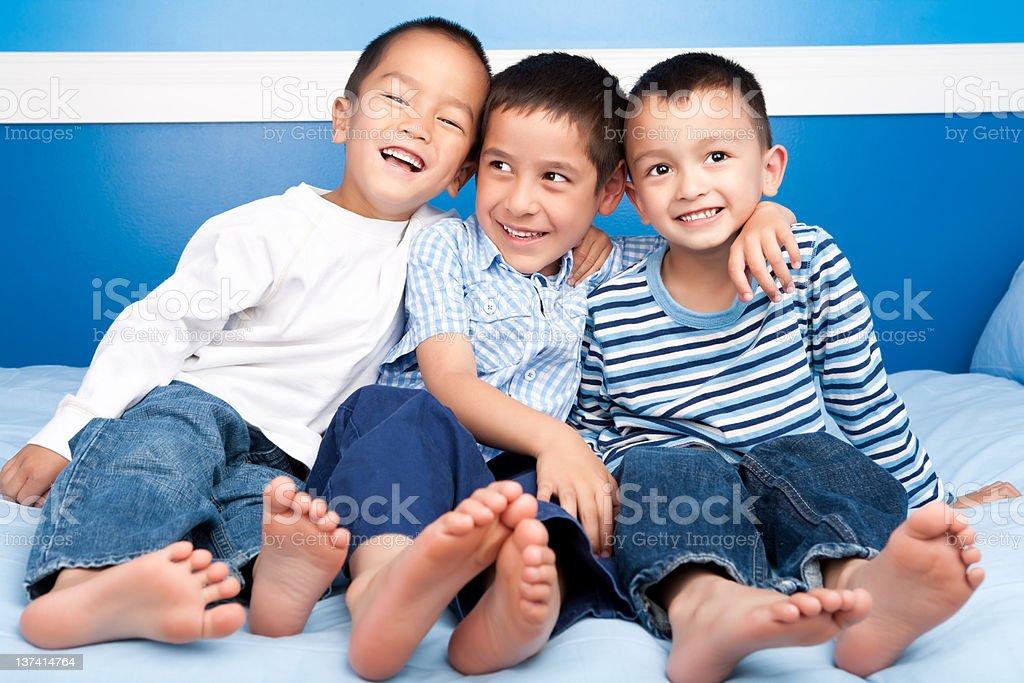 Three smiling asian boys bedroom portrait stock photo