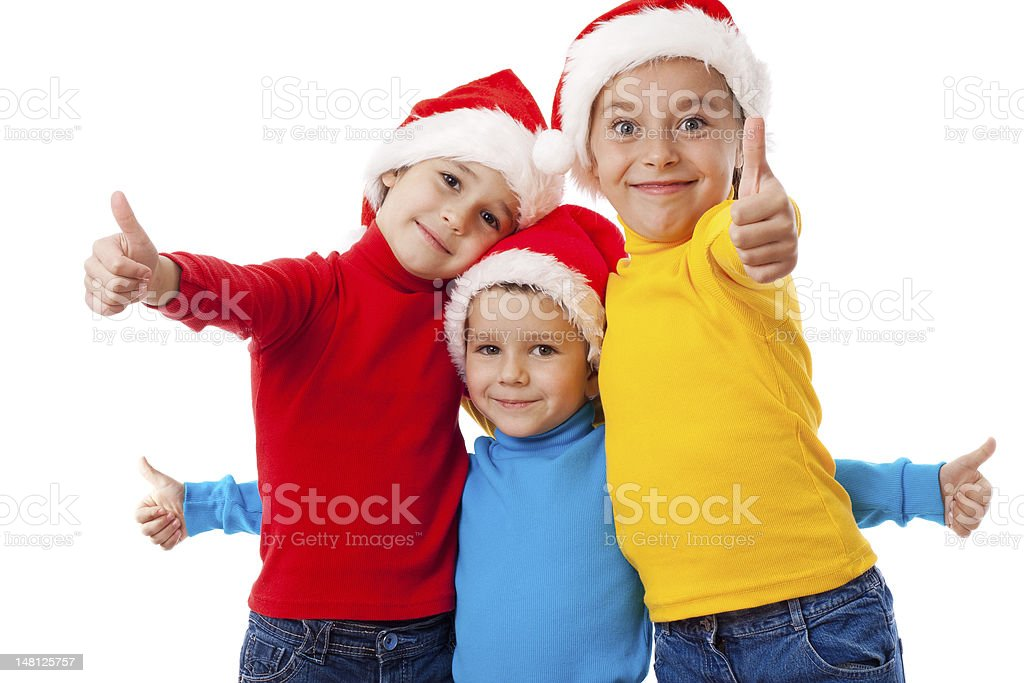 Three smiling children in Santa hats with thumb up sign royalty-free stock photo