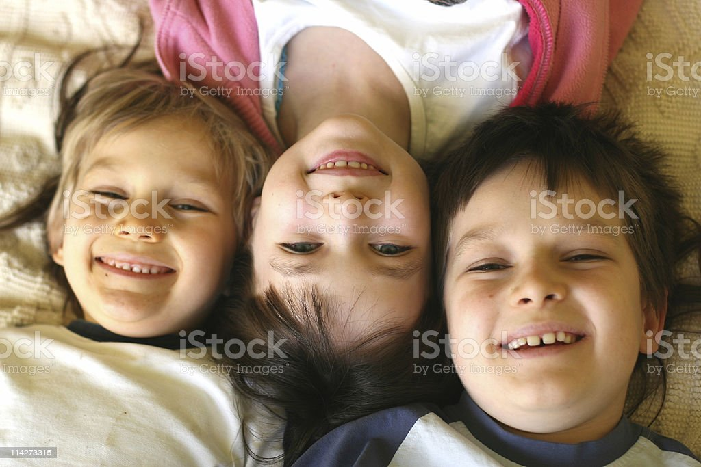 Three smiling children laying with their heads together stock photo