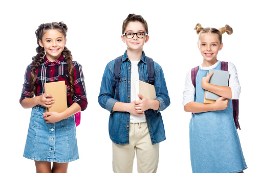 1016623732 istock photo three smiling classmates holding books and looking at camera isolated on white 1016623310