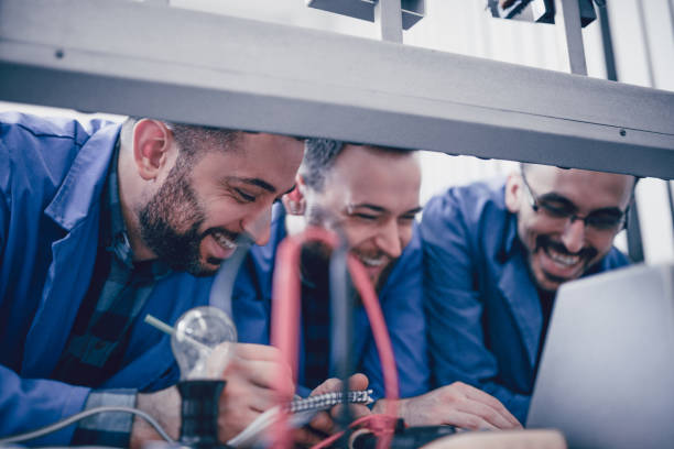 drei lachende ingenieure arbeiten an einem projekt in einer fabrik - versuche nicht zu lachen stock-fotos und bilder