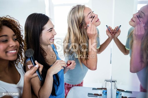 istock Three smiling friends putting makeup on together 846370896