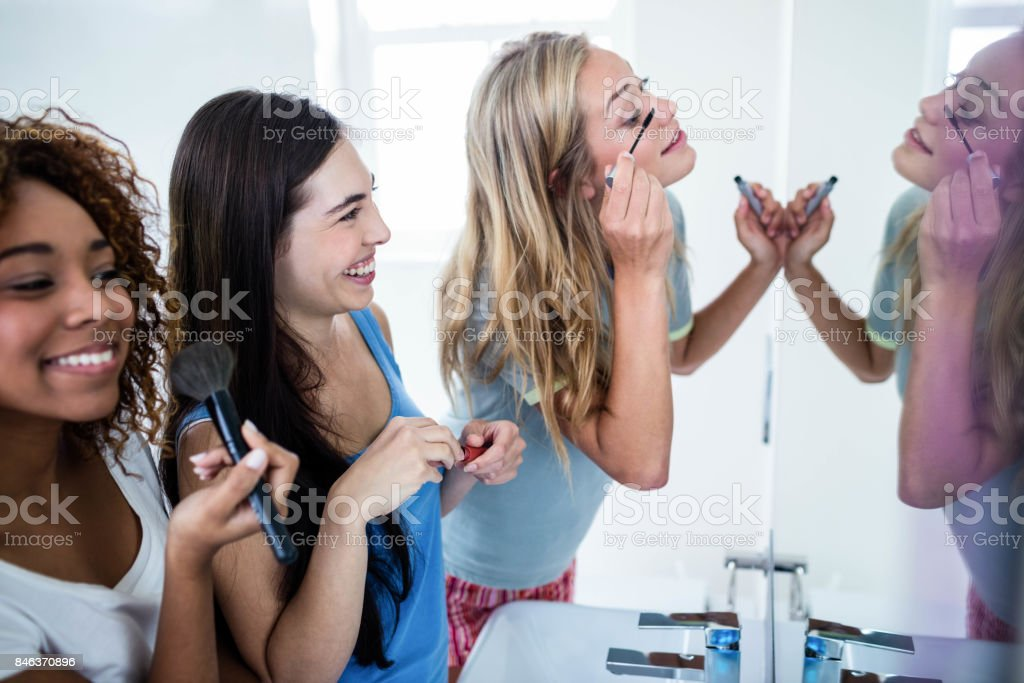 Three smiling friends putting makeup on together stock photo