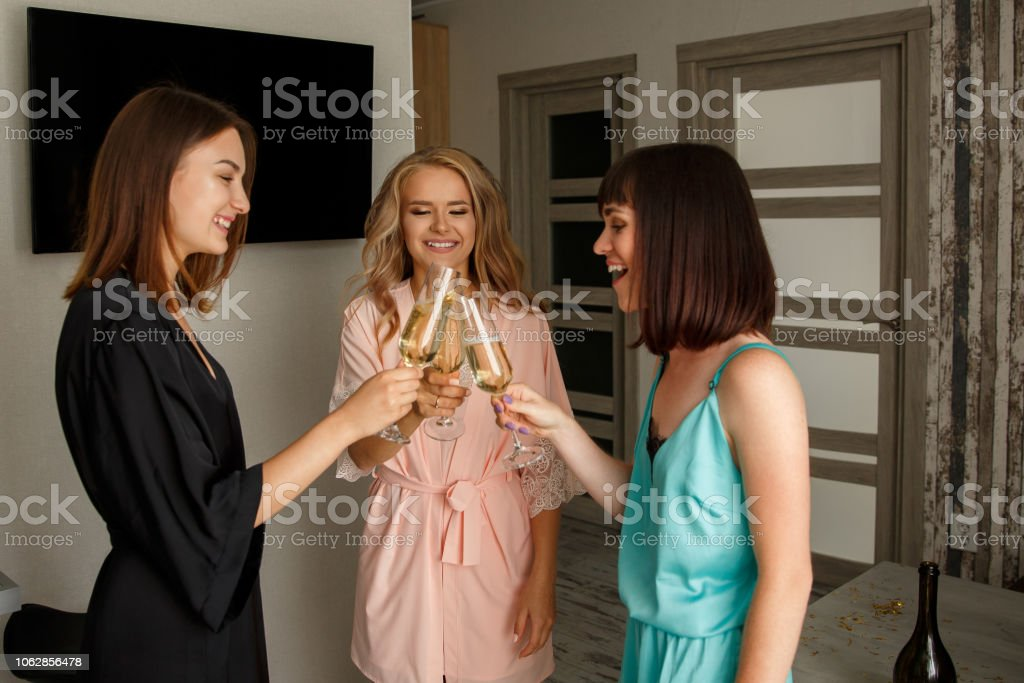 Three smiling girls celebrating bridal shower at home stock photo