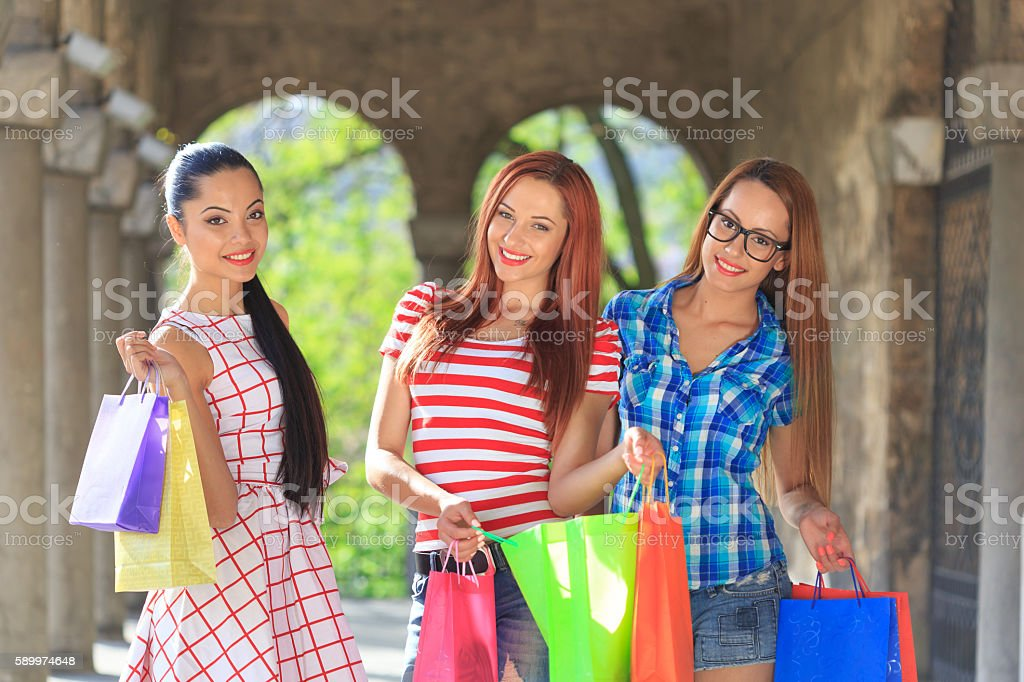 Three smiling girls with their new purchases stock photo