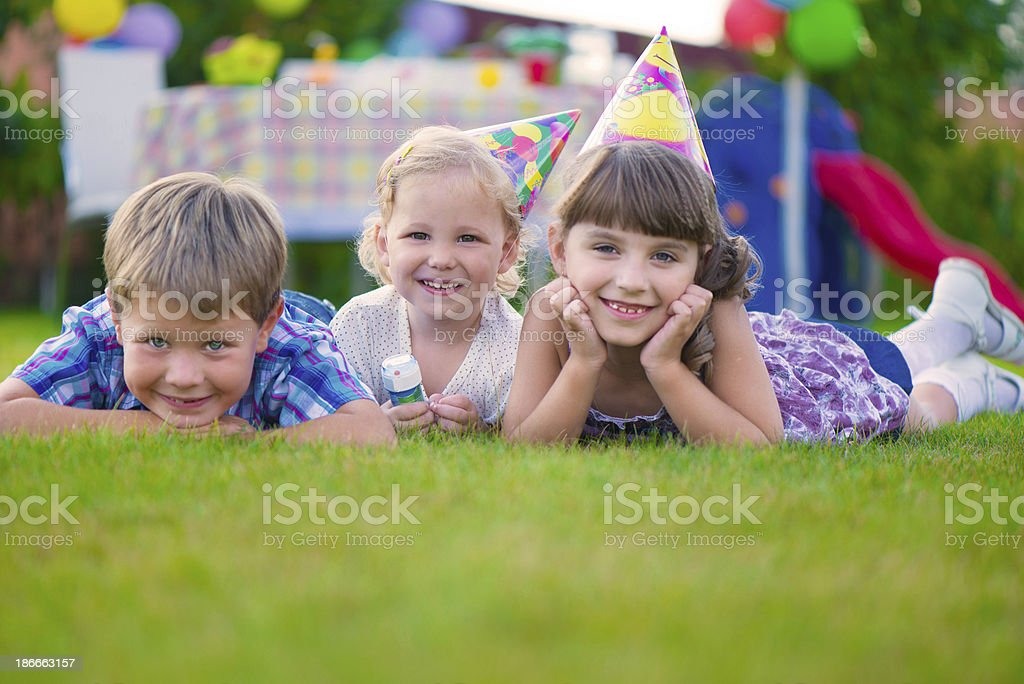 Three smiling kids laying in the grass at a birthday party stock photo