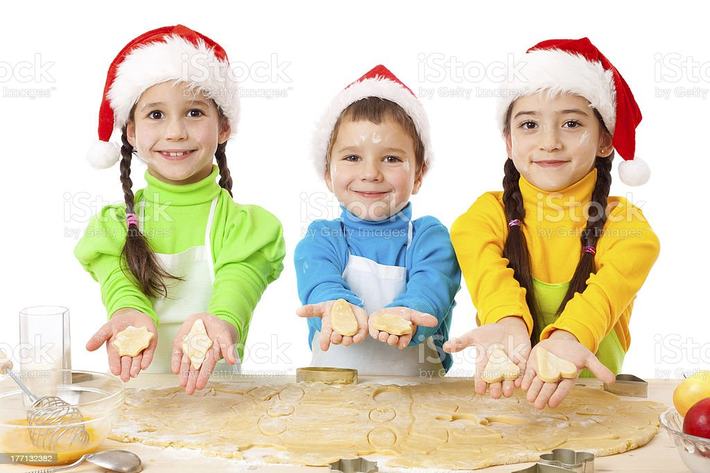 Three smiling kids showing Christmas cooking royalty-free stock photo