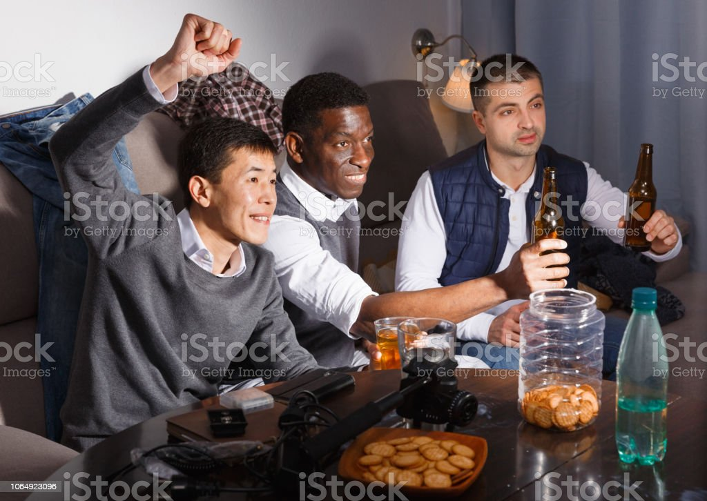 Three smiling men are watching TV and cheering for football team at...
