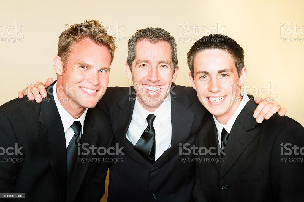Three smiling men in black suits portrait stock photo