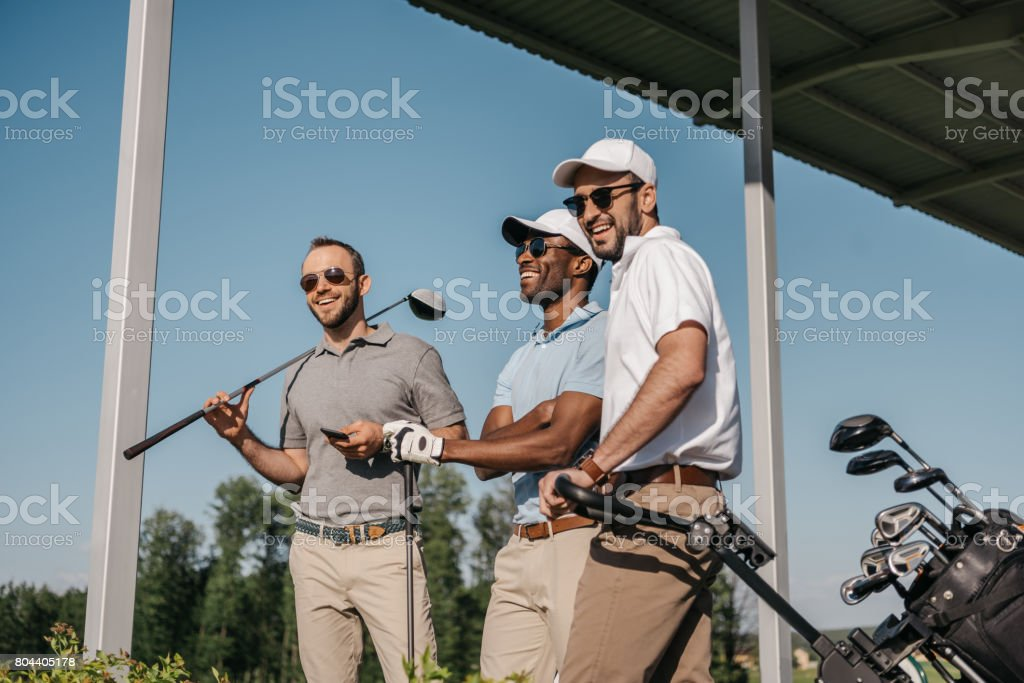 Three smiling men in sunglasses holding golf clubs outdoors stock photo