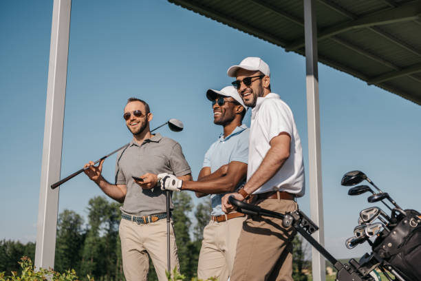 three smiling men in sunglasses holding golf clubs outdoors - golf stock photos and pictures