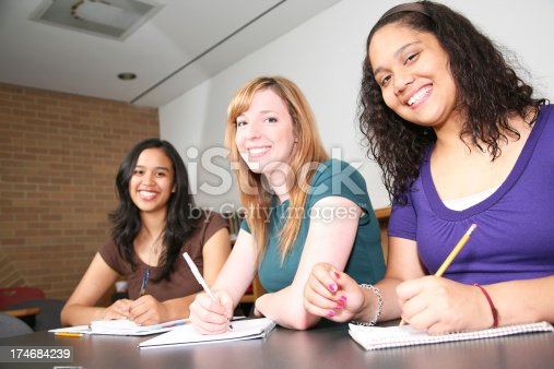 488149772istockphoto Three Smiling Students Taking Notes 174684239