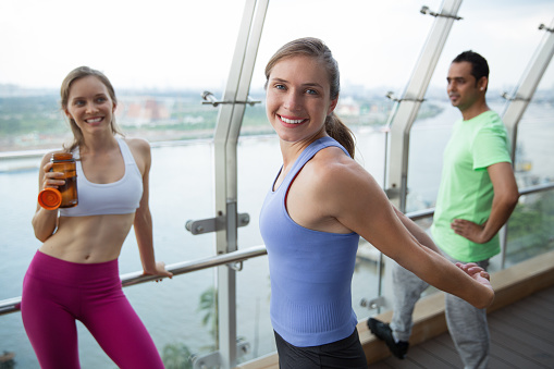 Three Smiling Young People Relaxing After Training Stock Photo - Download Image Now - iStock