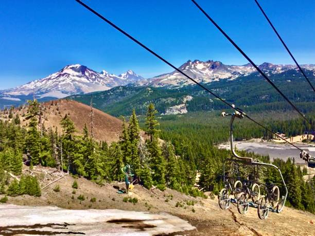 three snowcapped sisters / three trail bikes / three wires ski lift at mt. bachelor, bend, or samuel howell stock pictures, royalty-free photos & images