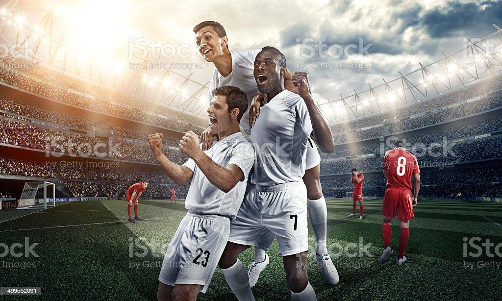 Three soccer players celebrate inside a stadium royalty-free stock photo