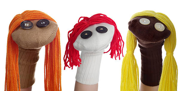Three Sock Puppets in a Row on a White Background Horizontal image of three sock puppets lined in a row on a white background. One puppet was created using a tan sock with orange hair, one puppet was made with a white sock and red hair, the third puppet was created with a dark brown sock with yellow hair. Their heads are tilted different directions giving them different expressions. puppet stock pictures, royalty-free photos & images