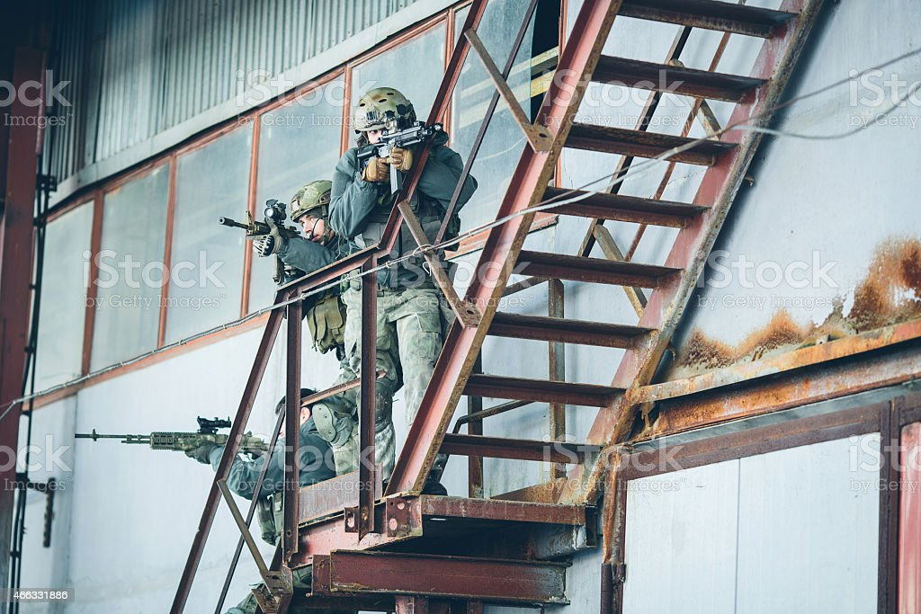 three soldiers climb the stairs at the factory stock photo