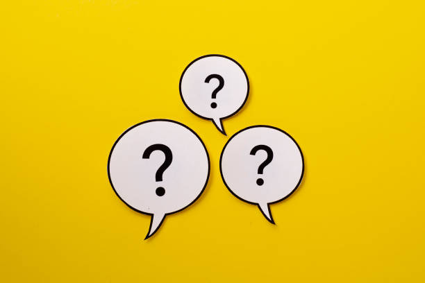 Three speech bubbles with question marks stock photo