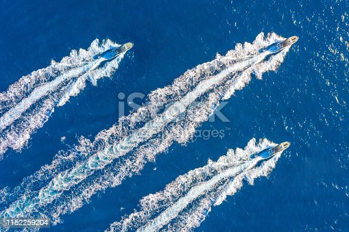 Three speed boats launch at high speed floats in the ocean, aerial top view