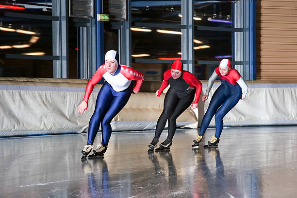 Three speed skaters stock photo