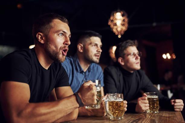 Drei Sportfans in einer Bar beim Fußballschauen. Mit Bier in der Hand – Foto