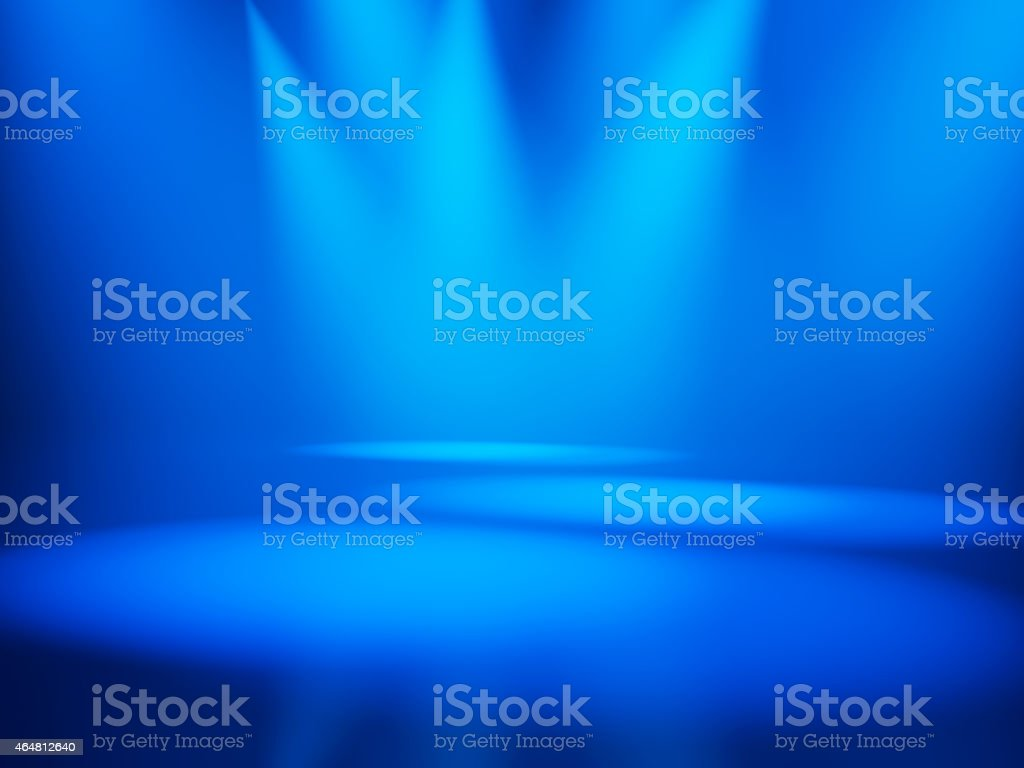 Three spotlights illuminate and empty, blue stage stock photo