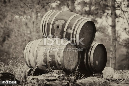 Three wine barrels stacked outside on their sides.  Sepia.