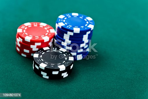 Three stacks of poker chips on card table.
