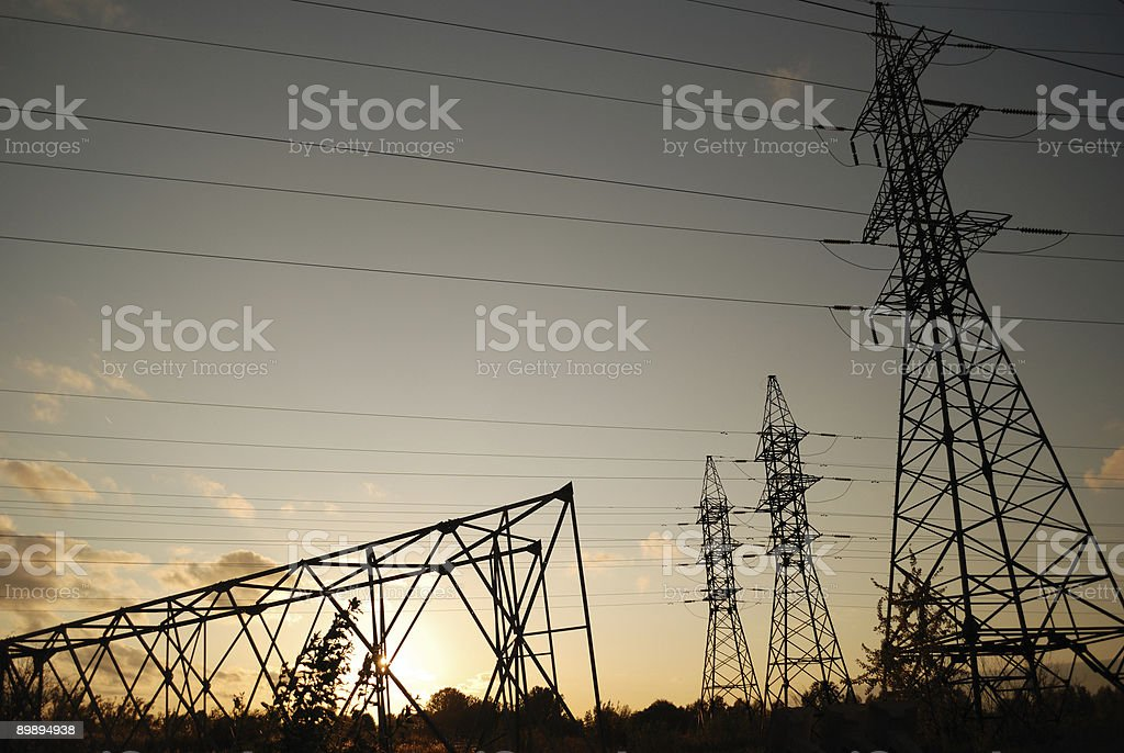 Three standing electrical towers and one fallen royalty-free stock photo