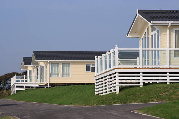Three static holiday homes or caravans Three holiday homes perched on a grass bank with verandas and a road. manufactured housing stock pictures, royalty-free photos & images