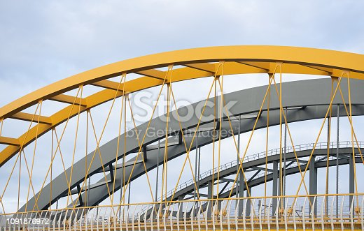 Three steel arch bridges lie side by side and span a river. One of the bridges is strikingly yellow in color and is the only suspension bridge. The other bridges are more traditionally constructed.