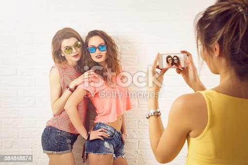 1092709104istockphoto Three Street Style Hipster Girls Taking Pictures 584848874