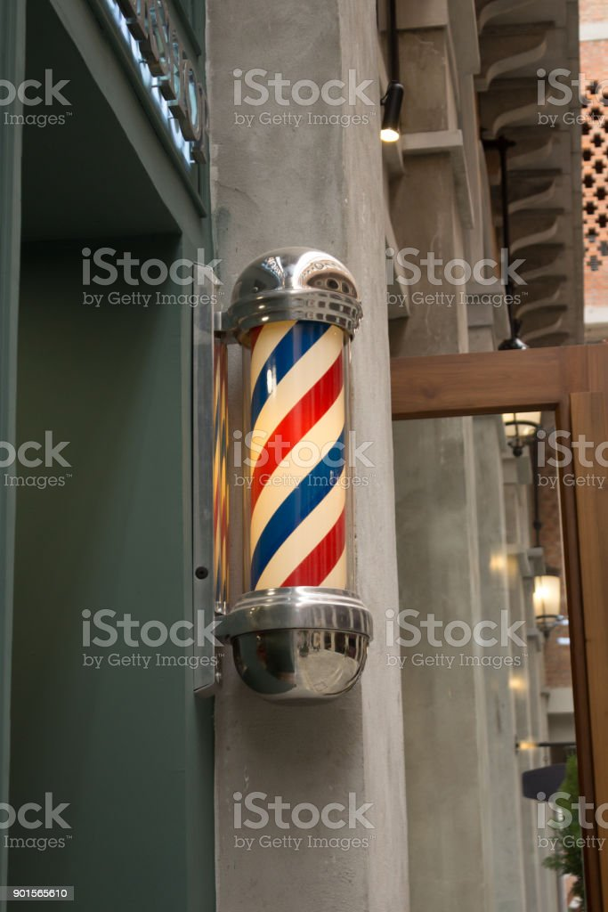 Three Striped Blue White Red Vintage Barber Pole Sign With Yellow Light Inside stock photo