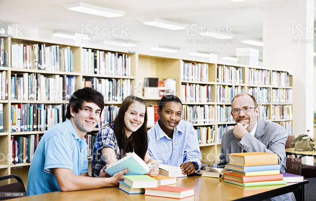 Three students and lecturer in library look up smiling royalty-free stock photo