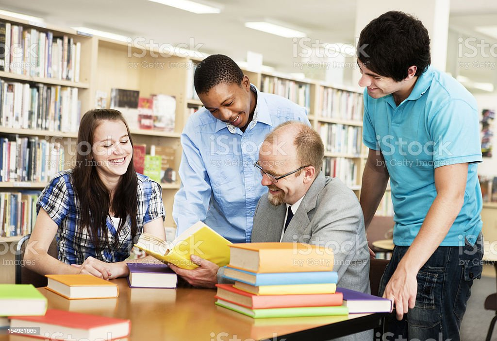 Three students and professor working happily together in library royalty-free stock photo