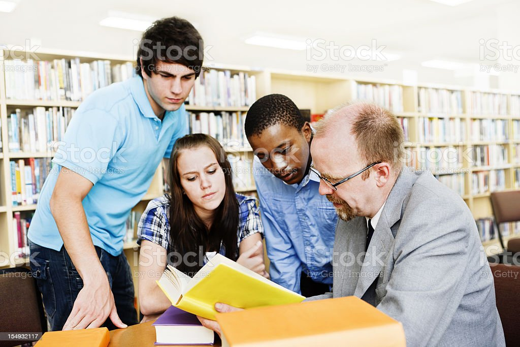Three students and teacher work together in library