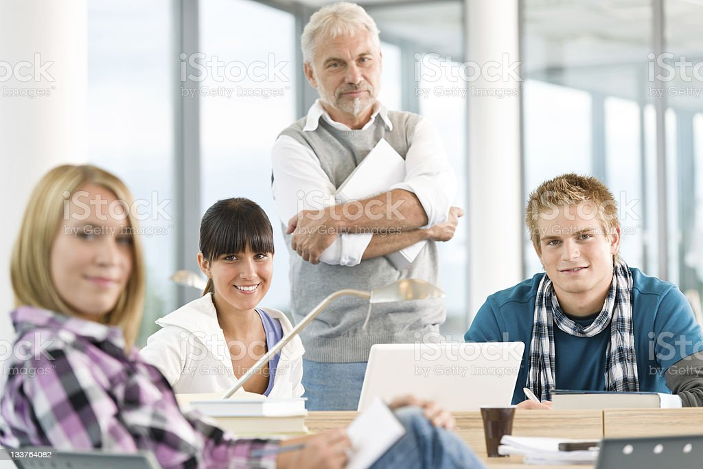 Three students and their professor smiling at camera royalty-free stock photo