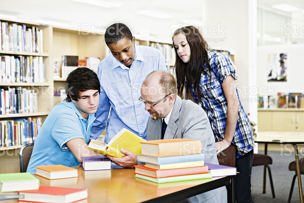 Three students and their teacher study together in library royalty-free stock photo